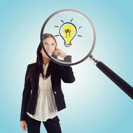 Magnifying glass examines the idea of a young businesswoman