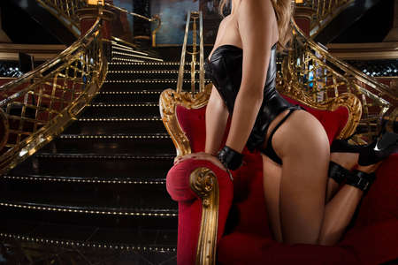 Sensual provocation of a sexy bdsm woman on an armchair Standard-Bild - 116092858