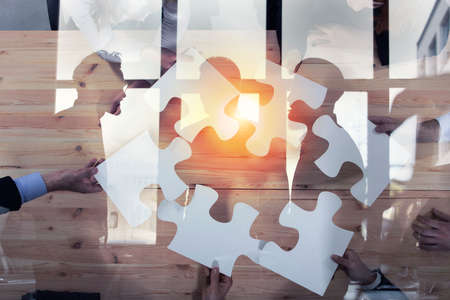 Business people work together to build a puzzle. Concept of teamwork, partnership, integration and startup. double exposure