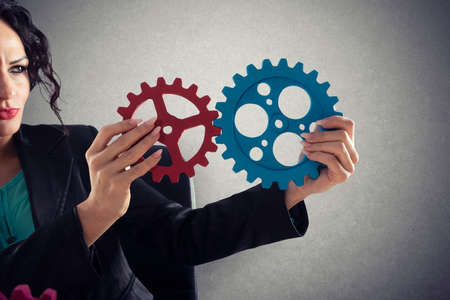 Businesswoman tries to connect gears pieces. Concept of Teamwork, partnership and integration Stock Photo