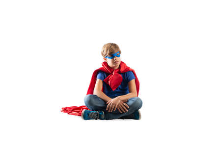 Superhero kid sitting on a wall that dreams. Isolated on white background