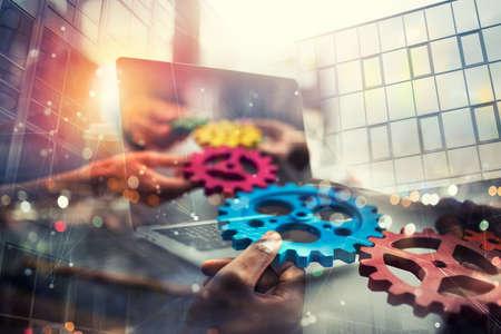 Gente de negocios con engranajes en mano que salen de una computadora portátil. concepto de cooperación remota y trabajo en equipo. Exposición doble