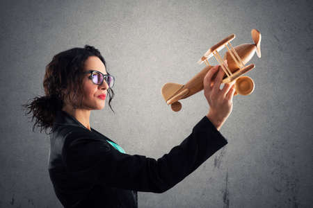 Businesswoman play with a toy aircraft. Concept of company startup and business success