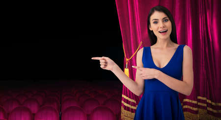 Pretty woman in front of red curtains indicates something about the theater show Imagens - 116758225