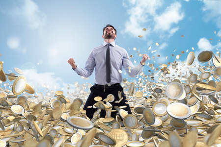 Businessman exults over a lot of money coins Stockfoto