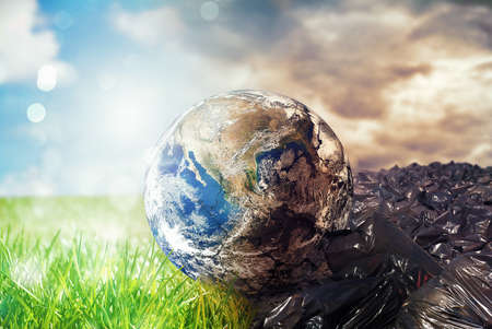 Earth is chancing due to pollution and undifferentiated trash. Save the World. World provided by NASA 免版税图像