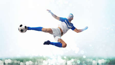 Soccer striker hits the ball with an acrobatic kick in the air on white