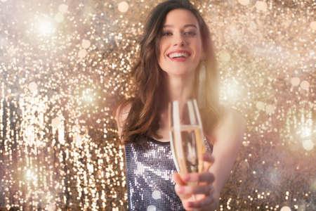 La ragazza beve lo spumante per festeggiare il nuovo anno Archivio Fotografico