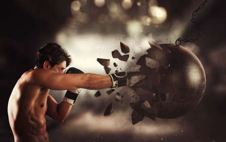 Power and determination of a young muscular boxer against a wrecking ball Stock Photo