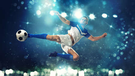 Soccer striker hits the ball with an acrobatic kick in the air on dark blue