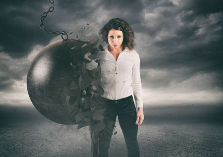Power and determination of a young business woman against a wrecking ball
