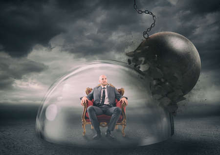 Businessman safely inside a shield dome during a storm that protects him from a wrecking ball. Stock Photo