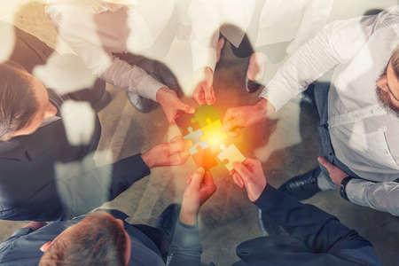 Les gens d'affaires se joignent aux pièces du puzzle. Concept de travail d'équipe et de partenariat. double exposition.