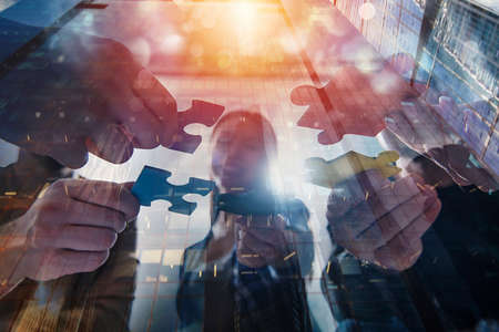 Business people join puzzle pieces. Concept of teamwork and partnership. double exposure
