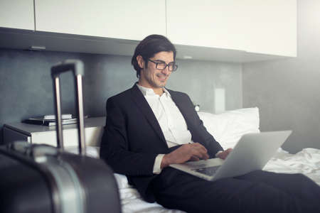 Businessman ready to travel works with his laptop