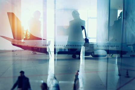 Silhouettes of businessman at the airport who waits for boarding. Double exposure