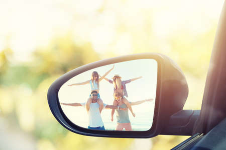 Wing mirror of a car with reflected a group of friends Stock Photo