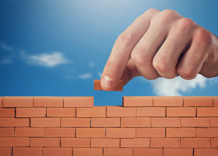 Businessman puts a brick to build a wall. Concept of new business, partnership, integration and startup Imagens - 119655825