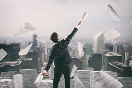 Businessman tired of bureaucracy throws up sheets of paper in the air