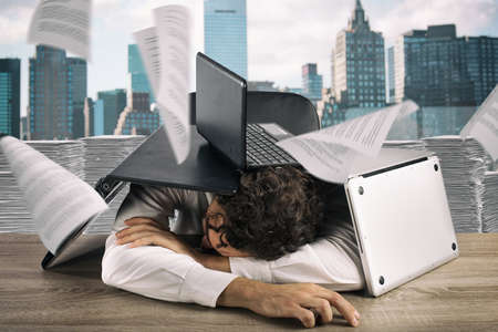 Tired businessman sleeping under a pile of laptops due to workload Stock Photo