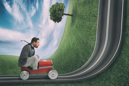 Businessman climb an uphill road with a small car. Difficult carrer concept