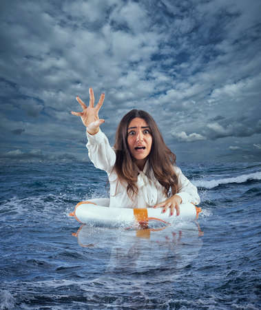 Businesswoman in the ocean with lifebelt asks help during a storm Reklamní fotografie