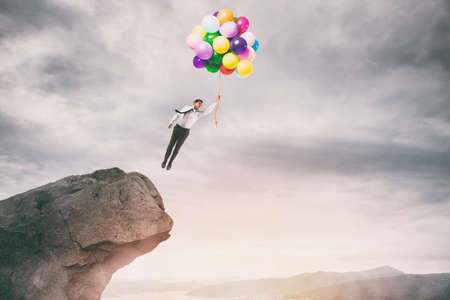 Creative businessman holding colorful balloons flies from the peak of a mountain Stock Photo