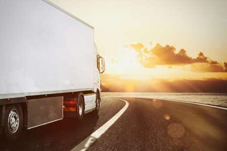 Witte vrachtwagen die bij zonsondergang op de weg rijdt in een natuurlijk landschap