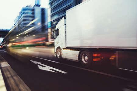 Biała ciężarówka porusza się szybko po drodze w nowoczesnym mieście z efektem świetlnym