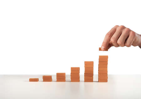 Businessman puts a brick on a bricks pile. Concept of growing statistics and success
