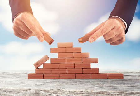 Businessman puts a brick to build a wall. Concept of new business, partnership, integration and startup Imagens - 120888197