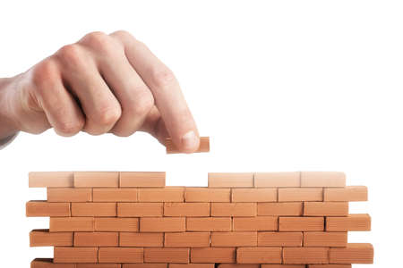 Businessman puts a brick to build a wall. Concept of new business, partnership, integration and startup Imagens - 120888201