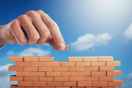 Geschäftsmann legt einen Ziegelstein, um eine Wand zu bauen. Konzept des Neugeschäfts, der Partnerschaft, der Integration und des Starts