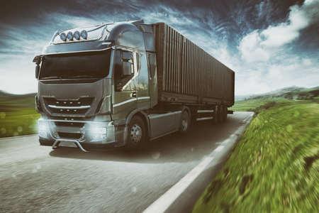 Grijze vrachtwagen rijdt snel op de weg in een natuurlijk landschap met bewolkte lucht