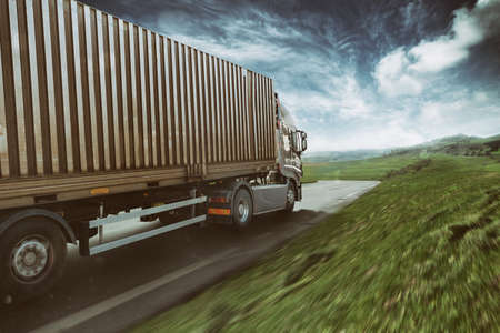 Grey truck moving fast on the road in a natural landscape with cloudy sky Stock Photo