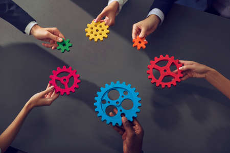 Business team connect pieces of gears. Teamwork, partnership and integration concept.