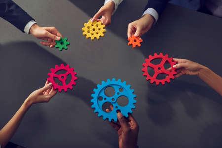 L'équipe commerciale connecte des pièces d'engrenages. Concept de travail d'équipe, de partenariat et d'intégration.