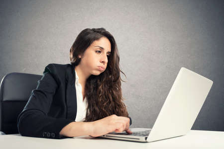 Bored woman snorts in the office while working on the laptop Stok Fotoğraf - 121237606
