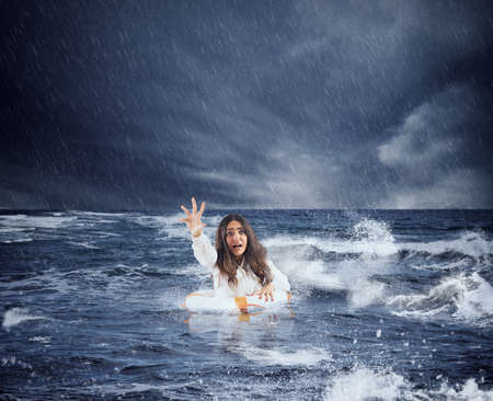 Businesswoman in the ocean with lifebelt asks help during a storm Stock Photo