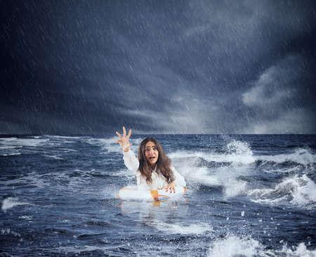 Une femme d'affaires dans l'océan avec une bouée de sauvetage demande de l'aide pendant une tempête