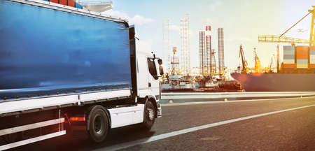 Camion voyageant rapidement vers un port commercial au coucher du soleil