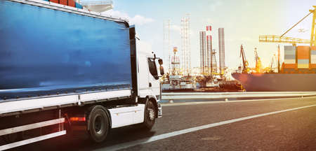 Truck traveling fast to a commercial port at sunset Stock Photo