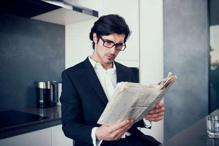 Businessman reads a newspaper at his home Foto de archivo - 121931311