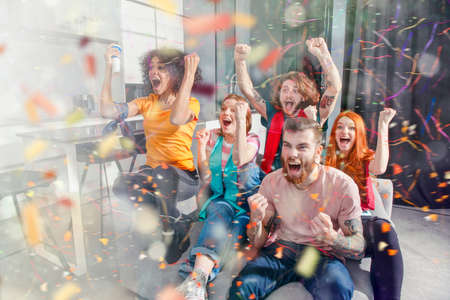 Amigos felices de los fanáticos del fútbol viendo fútbol en la televisión y celebrando la victoria con confeti cayendo