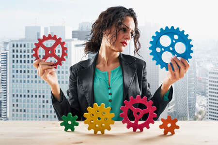 Businesswoman tries to work with gears. Concept of teamwork and partnership
