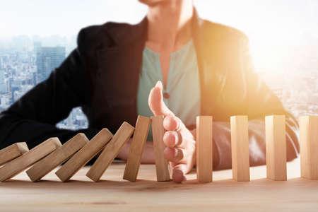 Geschäftsfrau stoppt einen Kettensturz wie ein Dominospiel. Konzept zur Verhinderung von Krisen und Misserfolgen im Geschäft.