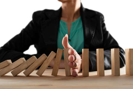 Businesswoman stops a chain fall like domino game. Concept of preventing crisis and failure in business.