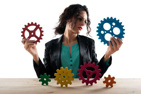 Businesswoman tries to work with gears. Concept of teamwork and partnership. Isolated on white background
