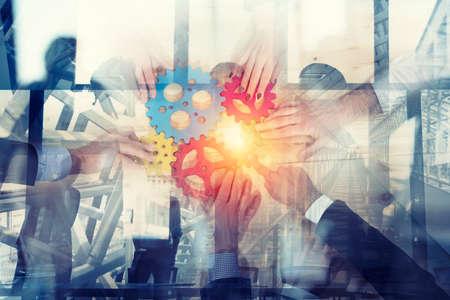 L'équipe commerciale connecte des pièces d'engrenages. Concept de travail d'équipe, de partenariat et d'intégration. double exposition Banque d'images