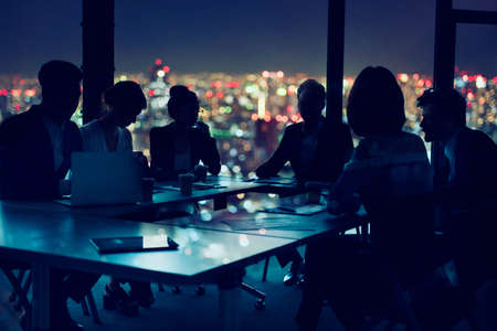 Businessmen that work together in office at night. concept of teamwork and partnership.